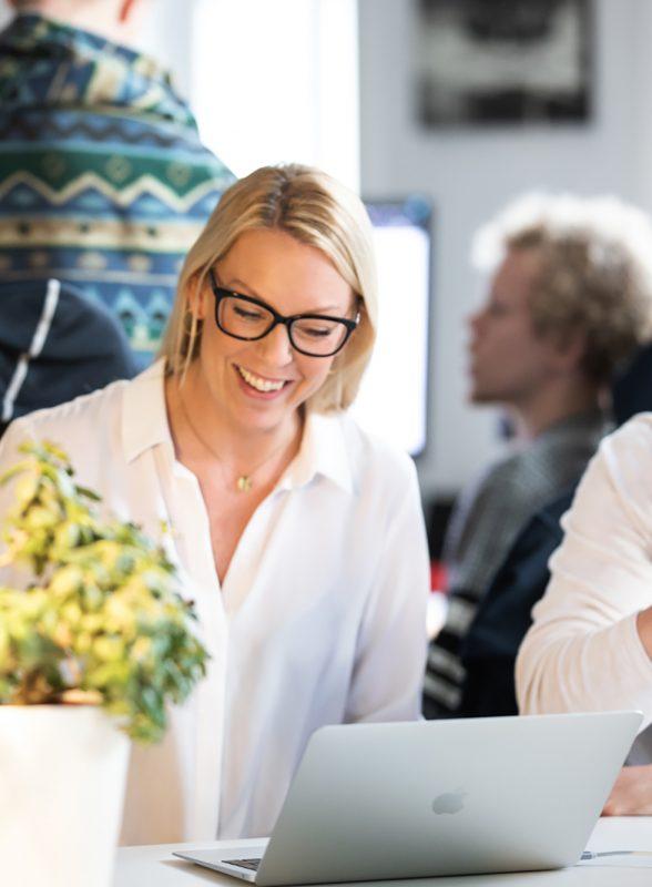 Kvinna som ler framför laptop